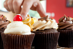 Close up of some decadent gourmet cupcakes frosted with a variety of frosting flavors.