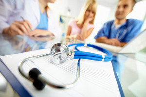 Close-up of stethoscope and paper on background of doctors and patient working with laptop