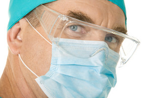 Close-up of surgeon wearing mask over white background