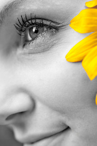 Close up of the face of a woman that is wearing a black eyed susan wildflower in her hair.  Selective color.