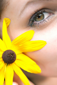 Close up of the face of a woman that is wearing a black eyed susan wildflower in her hair.  Shallow depth of field.