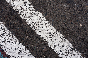 Close up of the twin white lines painted on the street asphalt.