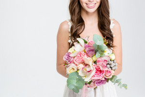 Close up of wedding bouquet of flowers holded by happy young bride with curly hair in white dress over white background