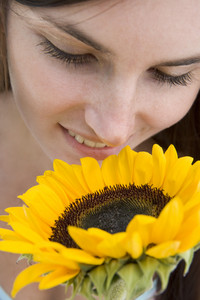 Close up of woman smelling sunflower