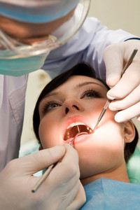Close-up of woman with open mouth being examined by hygienist