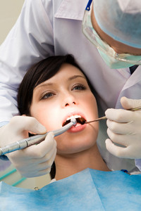 Close-up of young female with open mouth at the dentist office while doctor examining her oral cavity