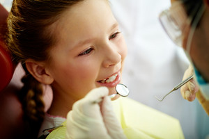 Close up portrait of a little smiling girl at dentist's office