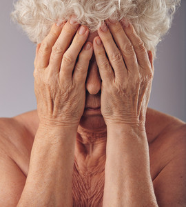 Close-up portrait of a sad looking senior woman with her head in her hands against grey background. Upset old woman covering her face.