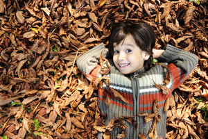 Close-up portrait of an beautiful autumn child laying on ground