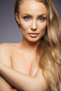 Close up portrait of attractive young woman posing against grey background. Caucasian young female model covering her breast with hands. Topless young with long blond hair.