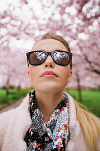 Close up portrait of attractive young woman wearing sunglasses looking up while at spring park. Stylish caucasian female fashion model.