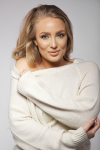 Close up portrait of beautiful young fashion model wearing sweater looking at camera. Young caucasian woman posing in oversized sweater on grey background.