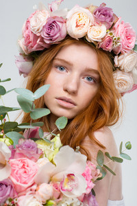 Close up portrait of beautiful young redhead woman in wreath of roses with flowers bouquet over white background