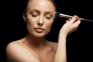 Close up portrait of beautiful young woman putting make up on with brush. Attractive female caucasian model on black background.