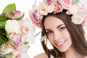 Close up portrait of pretty happy young woman in beautiful wreath of flowers over white background