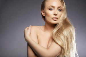 Close up portrait of sensual blond woman topless covering her breast with her hand with copy space. Caucasian female model with long blond hair looking at camera against grey background.