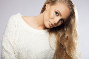 Close up portrait of young woman with long hair looking at camera. beautiful female fashion model wearing white sweater looking at camera on grey background.