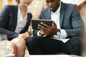 Close up shot of african business man showing something on digital tablet to his female colleague. Business people meeting in a coffee shop.
