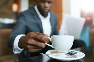 Close up shot of young man 's hand picking up cup of coffee. Businessman sitting at hotel lobby drinking coffee.