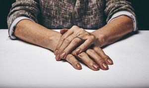 Close-up studio shot of a senior woman's hands resting on grey surface. Old lady sitting with her hands clasped on a table.