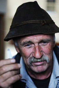Closeup Artistic Photo of Aged Man With  Grey Mustache Smoking Cigarette, grain added