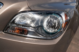 Closeup detail of a car headlight on a modern vehicle with metallic paint.