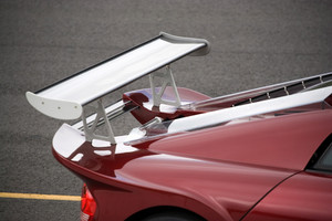 Closeup detail of a custom racing spoiler on the rear of a sports car.