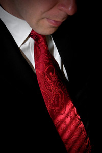 Closeup detail of a groom or business man in a tuxedo with a red tie.