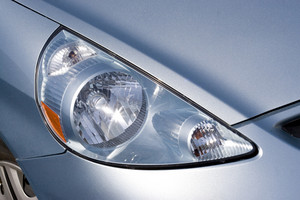 Closeup detail of a headlight on a modern vehicle with metallic paint.