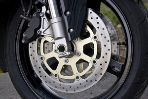 Closeup detail of a racing motorcyle's front wheel.  This is the brake caliper, rotor, rim, tire, and suspension.