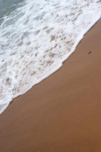 Closeup detail of the foaming sea waves washing ashore at the beach.