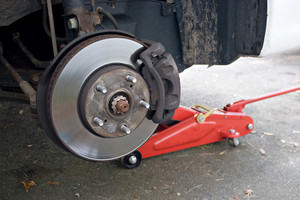 Closeup detail of the wheel assembly on a modern automobile.  The rim is removed showing the front rotor and caliper.