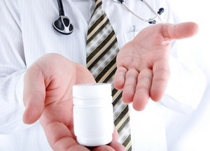 Closeup, doctor holding little pills bottle - copy space for you