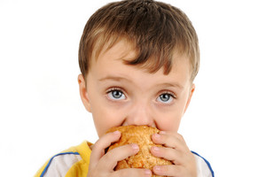 Closeup image of a cute kid eating sandwich