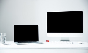 Closeup image of a laptop and PC on the workplace in office