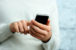Closeup image of a male hand holding smartphone and typing on it