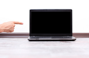Closeup image of a male hand pointing on the laptop screen