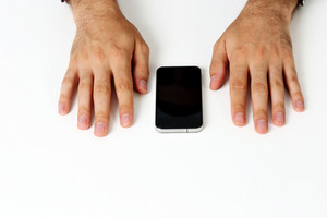 Closeup image of a male hands on a white table with smartphone