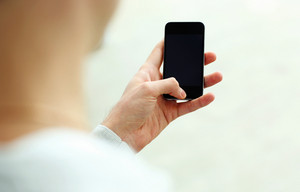 Closeup image of a man looking at blank smartphone display isolated on a white background