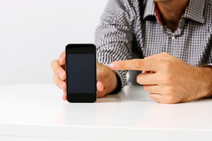 Closeup image of a man pointing on the smartphone screen