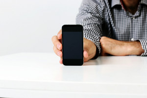 Closeup image of a man sitting at the table and showing smartphone screen