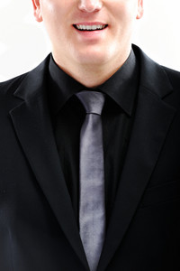 Closeup image of a smiling guy in black suit