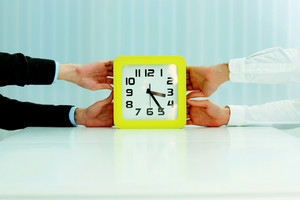 Closeup image of business hands pulling clocks