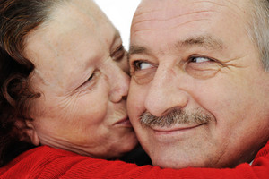 Closeup image of elderly woman kissing in a cheek her husband