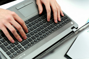 Closeup image of hands typing on laptop