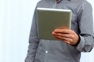 Closeup image of male hand holding tablet computer