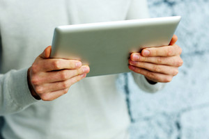 Closeup image of male hands holding tablet computer near the brick wall