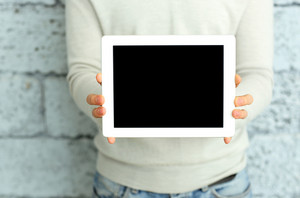 Closeup image of male hands showing display of tablet computer near the brick wall
