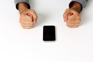 Closeup image of two fists on a white table with smartphone
