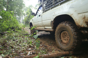 Closeup of 4x4 car driving uphill with mud